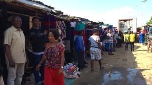 Ogwo Orgi Ogwo, vendeur de fripes au marché Missèbo à Cotonou, avec un de ses fils. Au fond, un camion rempli de ballots est déchargé.