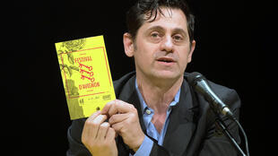 Olivier Py, the director of the Festival, holding up this year's program.