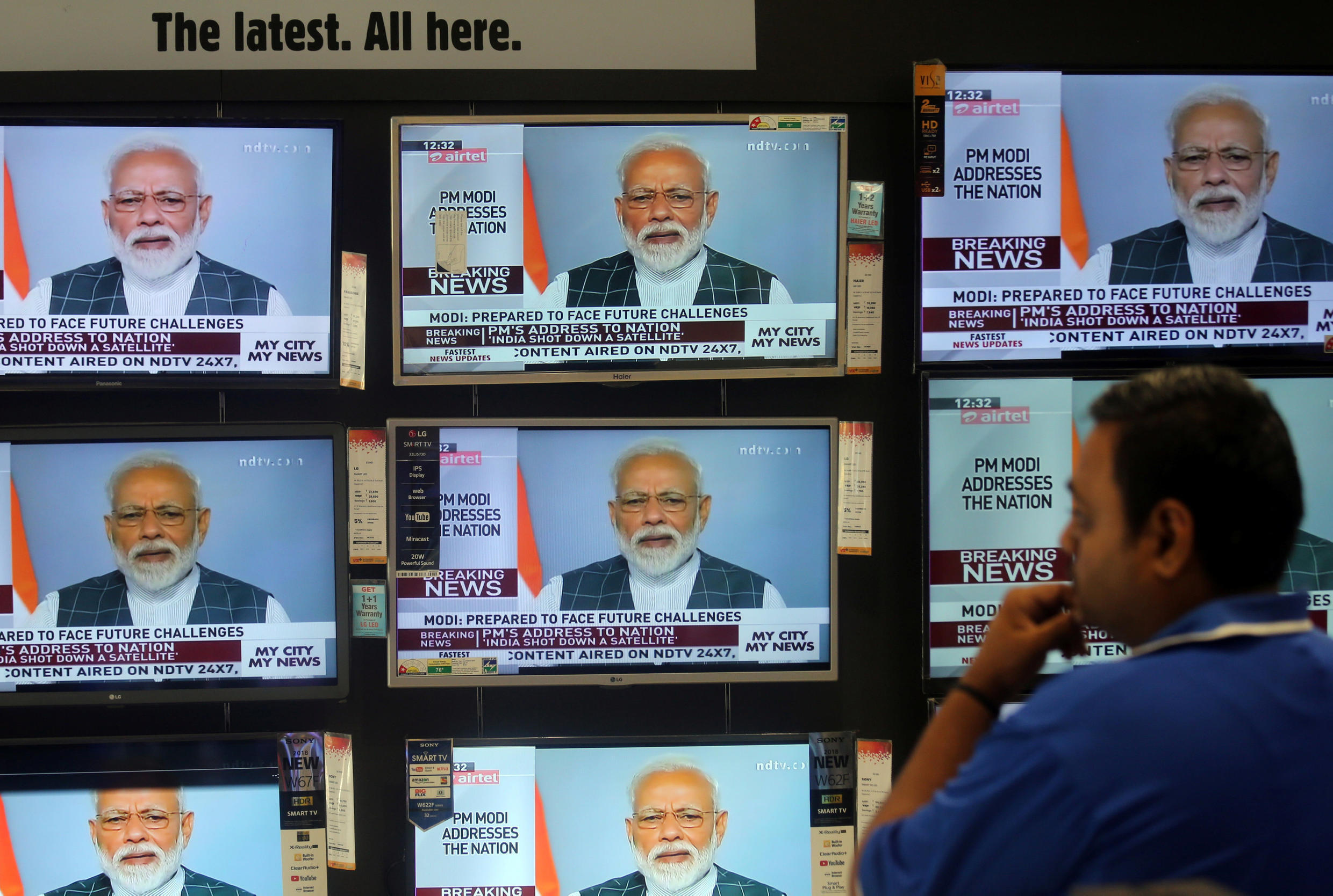 A man watches Prime Minister Narendra Modi addressing to the nation, on TV screens inside a showroom in Mumbai