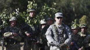 Un militaire américain et des soldats ukrainiens prennent part aux exercices militaires en dehors de la ville de Yavoriv, près le Lviv, le 19 septembre 2014.
