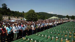 Les musulmans de Bosnie prient près des cercueils au mémorial de Potocari, près de Srebrenica, le 11 juillet 2012.