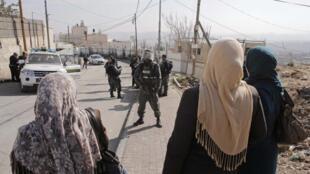 Wanawake wa Palestina pamoja na Askari polisi wa Israeli, kila upande ukiangalia mwengine, katika eneo la Jabal Al Mkaber, Jerusalem, Novemba 18 mwaka 2014.