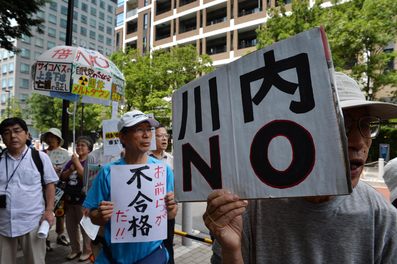 """Un manifestant anti-nucléaire brandit une pancarte """"Non à Sendai"""", à Tokyo, le 16 juillet 2014."""