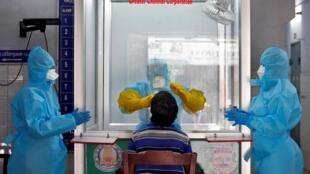 Un médecin dans une chambre de protection utilise un écouvillon sur un patient pour tester une éventuelle infection au coronavirus, dans un kiosque sans rendez-vous (WISK) nouvellement installé dans un hôpital public à Chennai, en Inde, le 13 avril.
