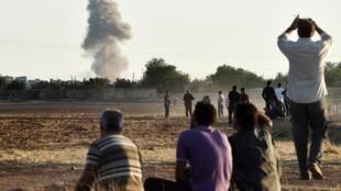 Curdos observam da fronteira com a Turquia os ataques do grupo Estado Islâmico em Kobane na terça-feira, 7 de outubro de 2014.