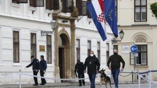 Des policiers inspectent le site de la fusillade à Zagreb, en Croatie, le lundi 12 octobre 2020. Un homme armé a tiré et blessé lundi un policier devant le siège du gouvernement croate dans la capitale, Zagreb, avant de se suicider.