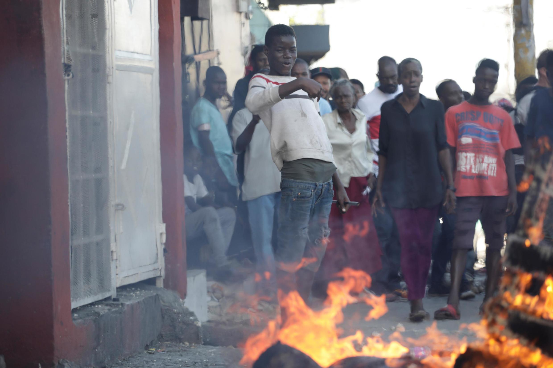 Port-au-Prince, le 27 octobre 2019. Un groupe de personnes contemple le brasier consumant le corps d'un homme mis à mort peu avant.