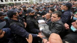 Un homme est porté par la police et des manifestants lors d'une manifestation marquant deux ans depuis le début du Hirak, à Alger, en Algérie, le 22 février 2021.