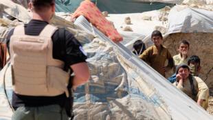 Des déplacés afghans devant un soldat américain, le 14 juin dernier.