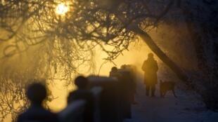 Mulher caminha com cachorro à beira de um rio congelado em Moscou, na manhã desta segunda-feira (24)