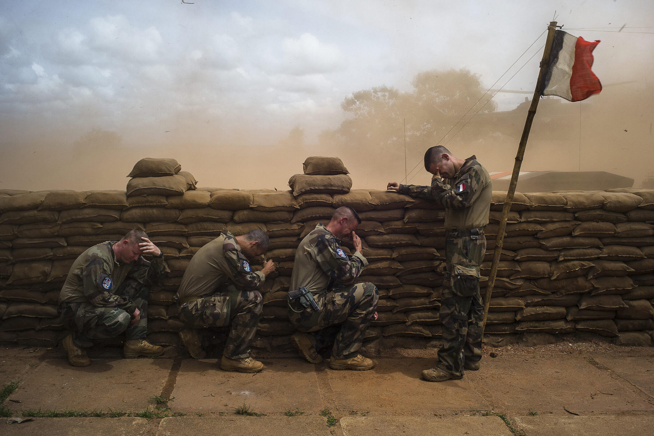 Soldiers sheltering behind sandbags while waiting for their commander. Bambari, Central African Republic, French outpost, August 16, 2014. Edouard Elias, winner of the Ville de Perpignan Rémi Ochlik Award 2015.