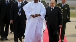 Amadou Toumani Touré (G), le président du Mali, accueilli par le président de l'Algérie, Abdelaziz Bouteflika (D), à l'aéroport international d'Alger le 24 octobre 2011.