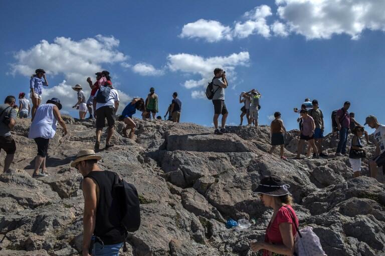 Les touristes visitent la colline d'Arès avec l'Acropole, à Athènes le 20 juillet 2018.