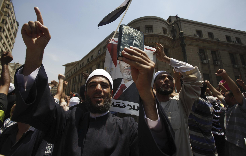 Un homme brandit un Coran lors d'une manifestation autour du palais de justice où seront jugés les six  Frères musulmans.