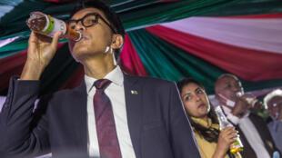 Le président malgache Andry Rajoelina boit du Covid-Organics,  à Antananarivo le 20 avril 2020, lors du lancement de ce remède traditionnel vanté pour ses effets préventifs et curatifs sur le coronavirus mais qui n'ont jamais été prouvés scientifiquement.