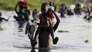 Children cross a body of water to reach a UN registration area in South Sudan.