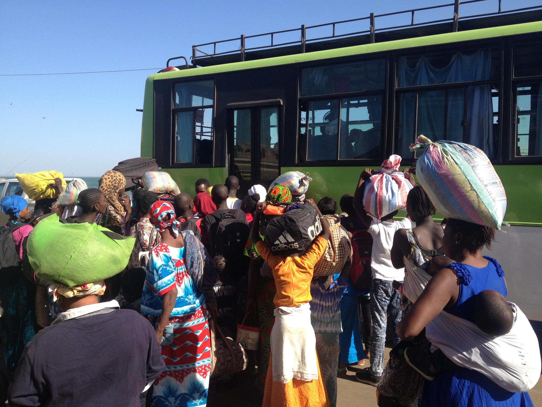 Returnees boarding a bus which will take them to Westfield, Serrekunda.