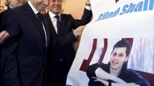 O presidente francês Nicolas Sarkozy retira cartaz que pede a libertação do soldado israelense Gilad Shalit, durante viagem a  Nice, no sul da França, nesta terça-feira.