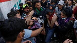 De nombreux médias ont été pris pour cible de manifestants. Ici, un manifestant blessé est évacué lors d'un rassemblement marquant un an depuis le début du mouvement de contestation irakien, le 25 octobre 2020 à Bagdad.