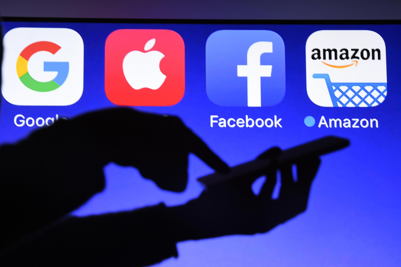 Una persona usa su teléfono móvil frente a los logotipos de Google, Apple, Facebook y Amazon que aparecen en una pantalla, el 28 de septiembre de 2017 en Hede-Bazouges, al oeste de Francia