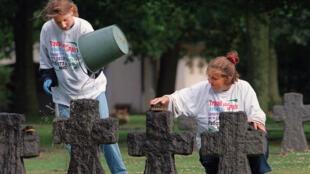 Des étudiantes allemandes nettoient les croix du cimetière militaire allemand de La Cambe, en Normandie.
