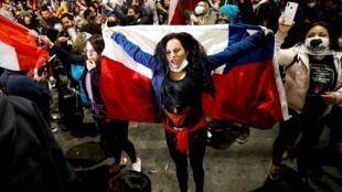 Une Chilienne fêtant les résultats du référendum portant sur une nouvelle Constitution, à Valparaiso, le 25 octobre 2020.