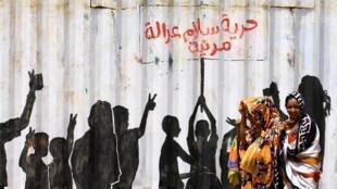 "Civilians walk past graffiti reading in Arabic ""Freedom, Peace, Justice and Civilian"" in the Burri district of Khartoum, Khartoum, Sudan, July 10, 2019."