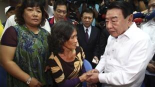 Chủ tịch Văn phòng Kinh tế và Văn hóa Manila (MECO) chia sẻ với vợ góa của ngư phủ Đài Loan bị thiệt mạng, ngày 08/08/2013.