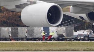 Des employés en train de charger un avion de transport de fret.