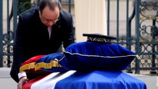 O presidente François Hollande se inclina diante do caixão do policial assassinado durante cerimônia em Versalhes.