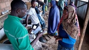 A newly arrived refugee from the DRC receives food ration at the Nakamira transit camp, northwest Rwanda
