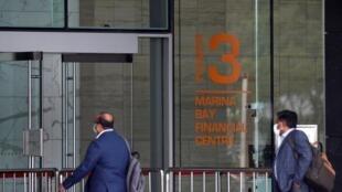 Des personnes entrent dans une tour du Marina Bay Financial Centre de Singapour, où se trouvent les locaux de la banque DBS.