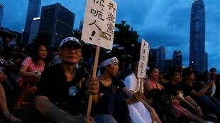 """A pro-democracy protester carries a placard which reads """"Communist Party, you lie!"""" as he sits with other protesters during a campaign to kick off the Occupy Central civil disobedience event in front of the financial Central district in Hong Kong August 31"""