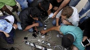Des réfugiés rechargent leurs téléphones à la frontière entre la Grèce et la Macédoine.