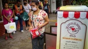 Des personnes font la queue pour recevoir de la nourriture gratuitement à Bangkok, en Thailande pays touristique durement touché économiquement par le coronavirus.