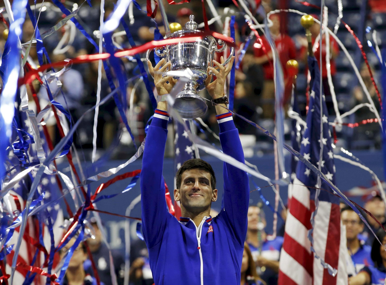 O tenista sérvio Novak Djokovic levanta a taça do US Open.