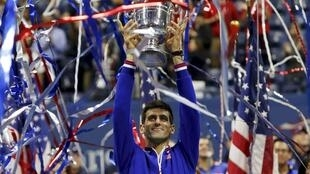 O tenista sérvio Novak Djokovic levanta a taça do US Open.