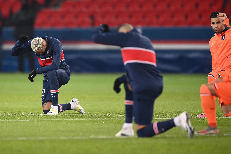 Os jogadores e árbitros do jogo entre PSG e Basaksehir turco ajoelham-se com os punhos levantados contra o racismo, antes de jogarem pelo Champions Group H no Parc des Princes, em Paris, em 9 de dezembro de 2020