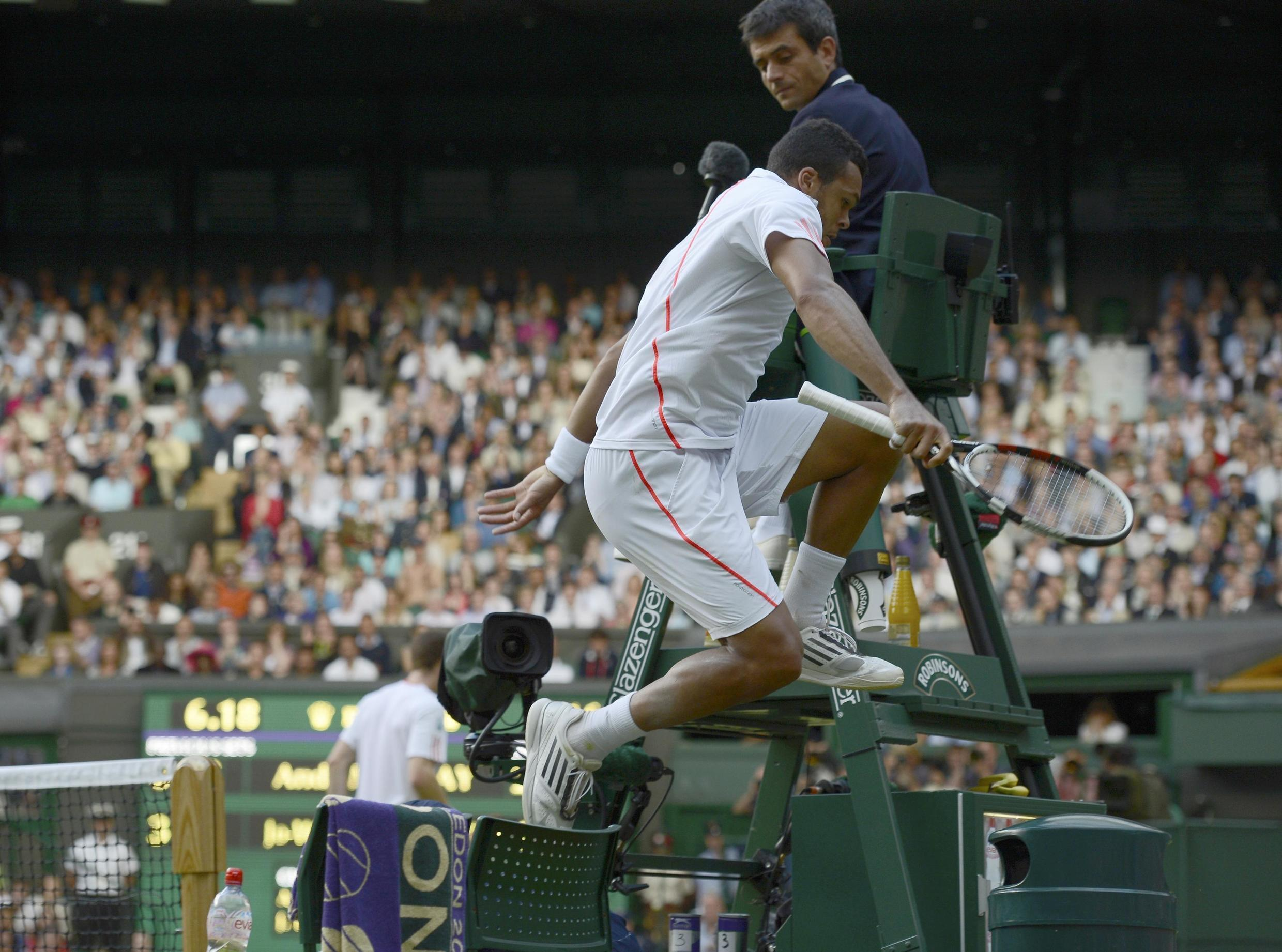 Jo-Wilfried Tsonga leaps over his chair during his men's semi-final tennis match against Andy Murray