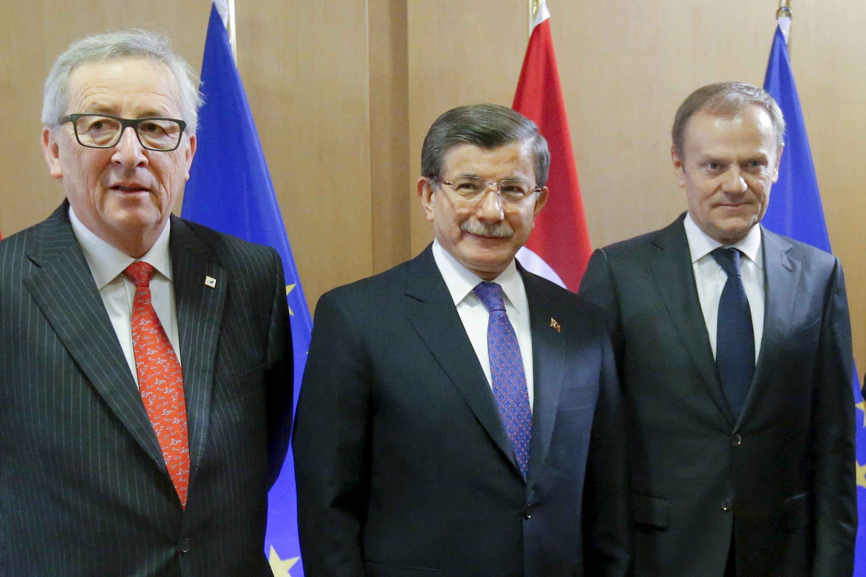 Ahmet Davutoglu, le Premier ministre turc (c) Jean-Claude Juncker, le président de la Commission européenne (g) et Donald Tusk, le président du Conseil européen lors de la signature de l'accord le 18 mars 2016, à Bruxelles.
