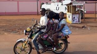 Une moto passe devant un véhicule blindé des Nations unies à Bangui, le 30 novembre 2015.