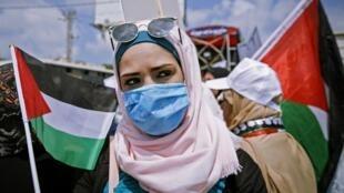 Femme palestinienne portant un masque lors d'une manifestation dans le nord de la Bande de Gaza, le 6 juillet 2020.