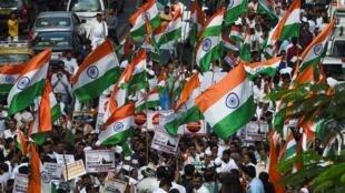 Des supporters du Congrès national indien brandissent des drapeaux indiens, pour commémorer les 134 ans de la fondation de leur parti et protester contre la loi sur la citoyenneté, le 28 décembre 2019, à Bombay.