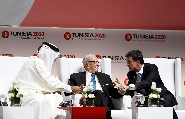 L'émir du Qatar, cheikh Tamim Ben Hamad al-Thani (G), et le Premier ministre français Manuel Valls (D) autour du président tunisien Beji Caïd Essebsi, lors de l'ouverture de la conférence Tunisia 2020. A Tunis, le 29 novembre 2016.