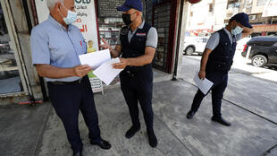 Un miembro del equipo del gobierno iraquí contra las noticias falsas entrega un panfleto a un hombre en Bagdad, el 20 de mayo de 2021