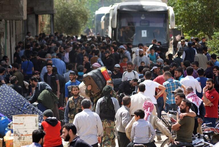 """به گزارش خبرگزاری دولتی سوریه، """"سَنا""""، اتوبوسهای بسیاری به این مناطق برای انتقال شورشیان به شمال سوریه فرستاده شده اند. به گفته این خبرگزاری، حدود پنج هزار تروریست و افراد خانواده شان باید این مناطق را ترک کنند."""