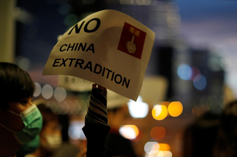 """香港大学生13日在立法会门前高举""""反对向中国引渡""""标语。"""