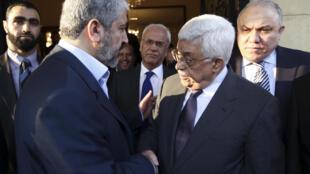 Poignée de main entre le leader du Hamas Khaled Mechaal (G) et le président palestinien Mahmoud Abbas (D) au Caire, le 24 novembre 2011.