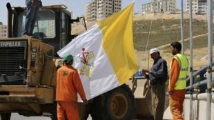 Le 23 mai 2014, des ouvriers s'apprêtent à hisser un drapeau du Vatican pour la visite du pape François à Amman.