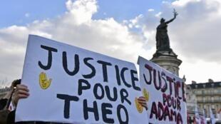 """Des manifestants tiennent une pancarte portant l'inscription """"Justice pour Theo, Justice pour Adama"""" lors d'une manifestation contre les violences policières qui s'est tenue le 18 février 2017 sur la place de la République à Paris."""